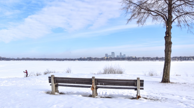 Park bench in snow by frozen lake with skier and skyline